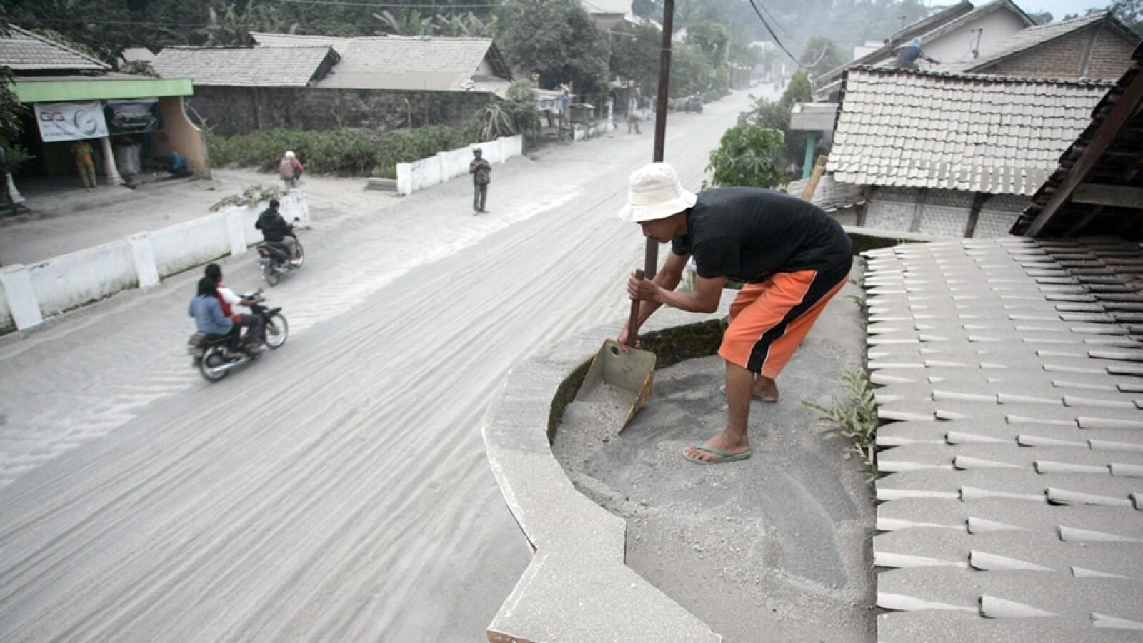 un hombre limpia su vivienda de cenizas