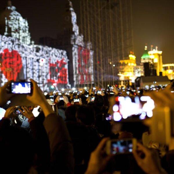 Visitantes tomaron fotografías y videos durante un espectáculo de luces en el Bund, una zona de altos edificios de la ciudad china.