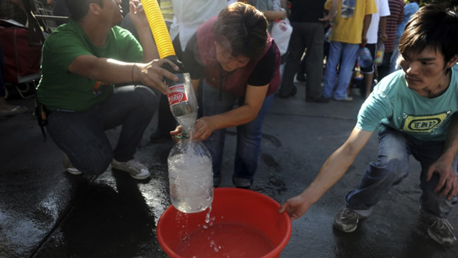 Un grupo de chilenos toma agua de una pipa. En las zonas más afectadas por el sismo el servicio no ha sido restablecido