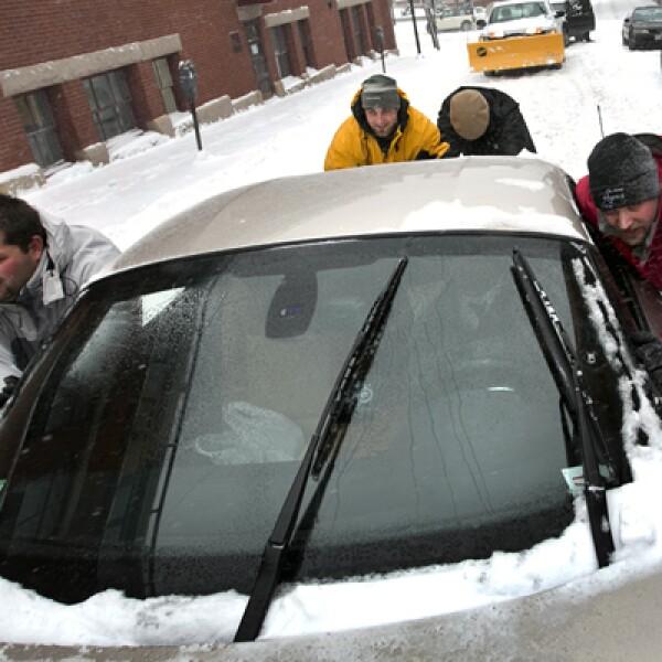 Millones de estadounidenses salieron temprano de sus trabajos por el temor a quedar varados en las carreteras. Un grupo de hombres en Portland ayuda a liberar un vehículo en la nieve.