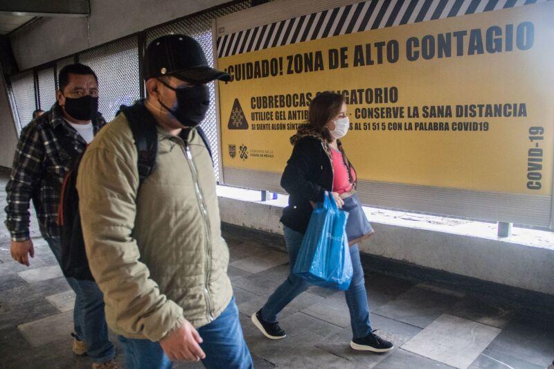 Usuarios del Metro, en la estación Politécnico terminal de la linea 5 del STC. Algunos hacen caso omiso de las recomendaciones para el uso de este transporte. Trabajadores de limpieza realizan la desinfección del tren.