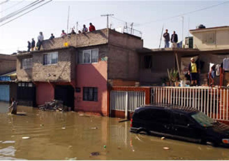 Habitantes de El Arenal se refugian en las azoteas mientras esperan que comience el desazolve del agua. (Foto: Notimex)