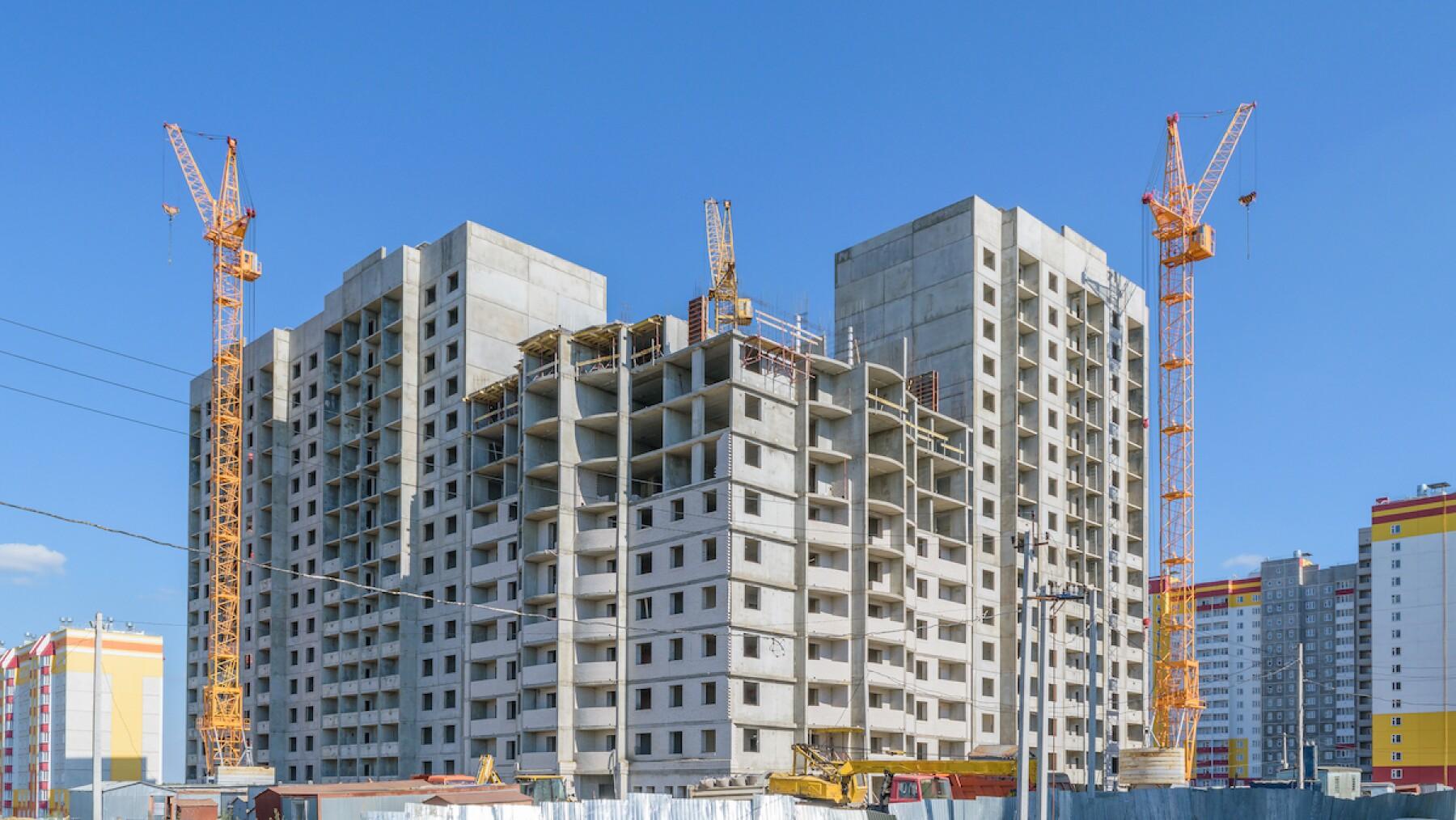 Construction of new multi-storey panel house. Three tower cranes