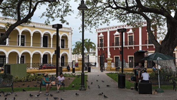 shoe cleaner and restless walkers in independence park in the old town of campeche, mexico