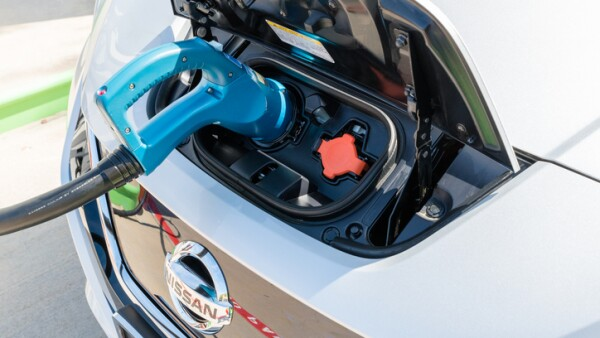 New 2018 Nissan Leaf electric car plugged in to charge battery at the EVgo charging station