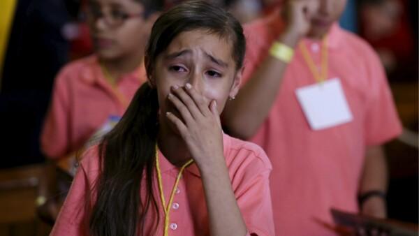 Una pequeña llora emocionada por la presencia del pontífice.