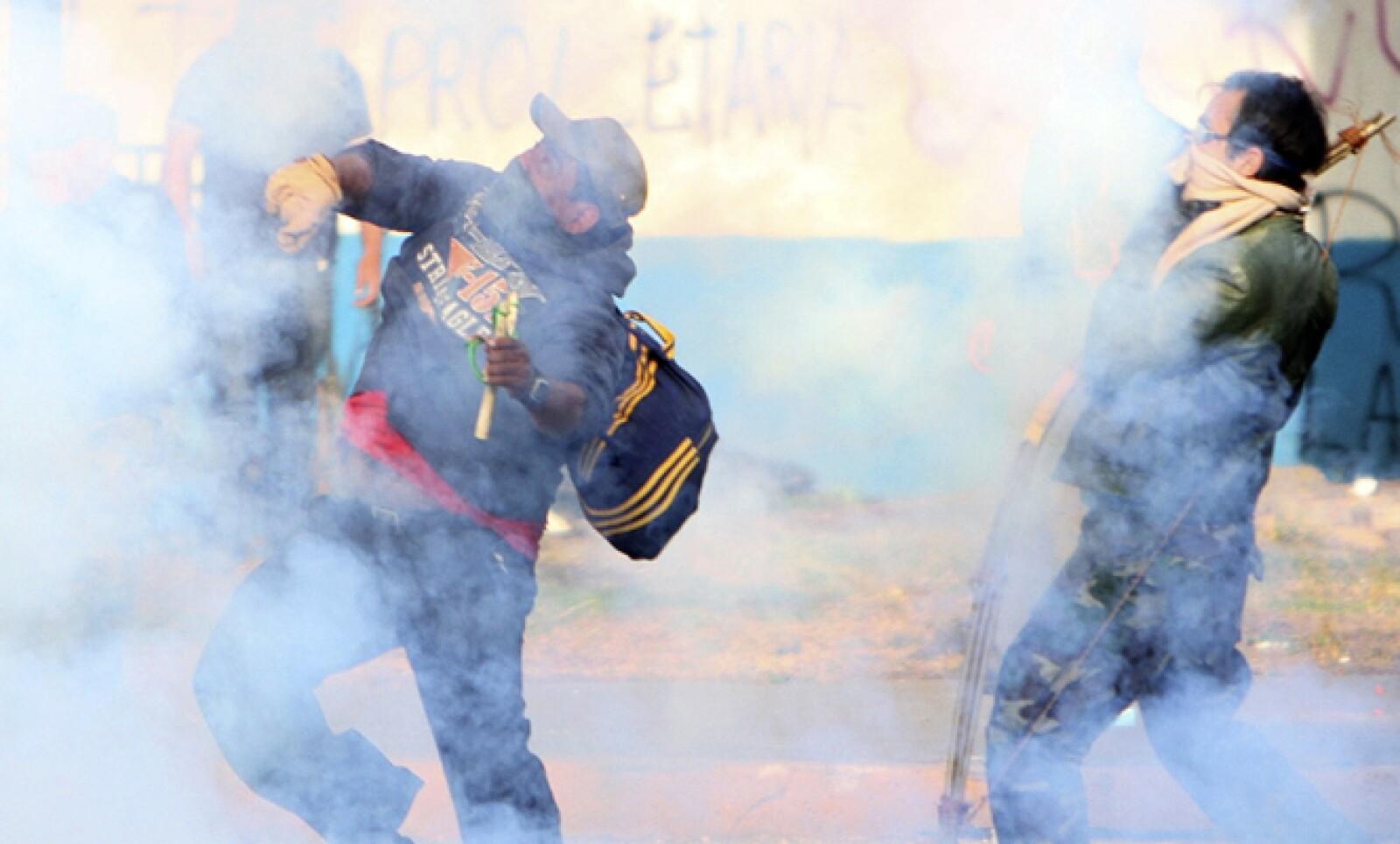 Con agua y extintores fue controlado el fuego momentáneo que generaron los activistas, y al parecer agentes de seguridad contestaron con gases lacrimógenos.