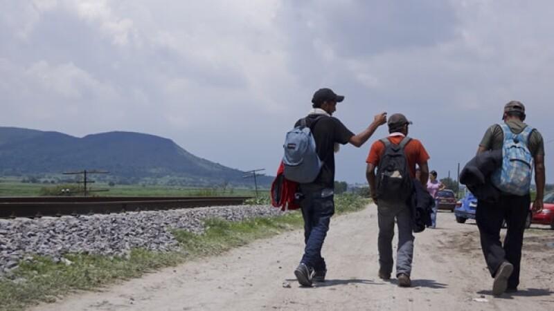 Migrantes caminan por vías del tren
