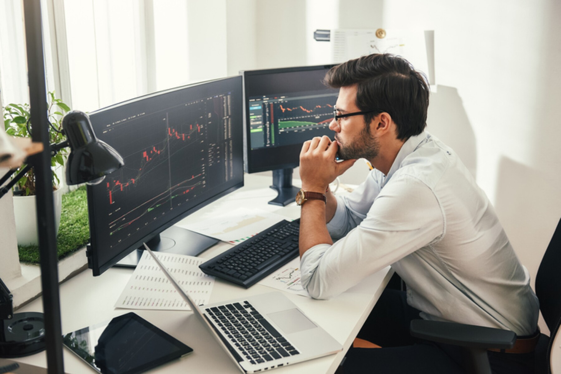 Successful trader. Back view of bearded stock market broker in eyeglasses analyzing data and graphs on multiple computer screens while sitting in modern office.
