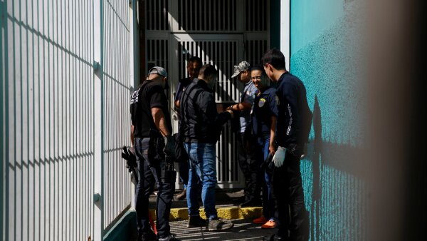 Criminal investigators look for evidence in a building after an explosion in Caracas