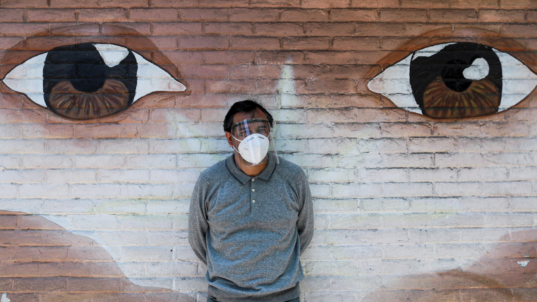 A journalist wearing a protective mask stands by a wall, as the outbreak of the coronavirus disease (COVID-19) continues in Xochimilco, Mexico City