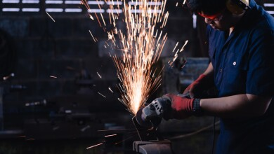 Immigrant manufacturing worker using angle grinder power tools on metal creating hot sparks wearing safety protective work wear