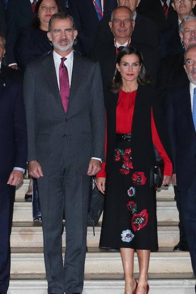 La Reina Letizia de Asturias hizo aparición en Sevilla con una blusa roja de manga larga, capa negra corta y una falda midi de estampado floral