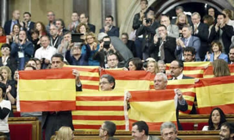 Diputados muestran banderas españolas y catalanas en el Parlamento de Cataluña tras aprobarse la resolución independentista. (Foto: EFE )