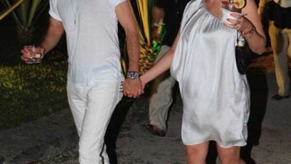 José María Torre porta una T-Shirt y pantalón blanco y zapatos color café, Cristina Lima también porta un vestido blanco holgado con un hombro descubierto, zapatos altos blancos con negro, bolso negro y cabello amarrado.