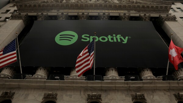 FILE PHOTO: The Spotify logo hangs on the facade of the New York Stock Exchange with U.S. and a Swiss flag as the company lists it's stock with a direct listing in New York