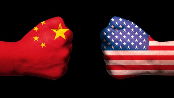 Flags of USA and China on two clenched fists facing each other on black background/usa china trade war concept