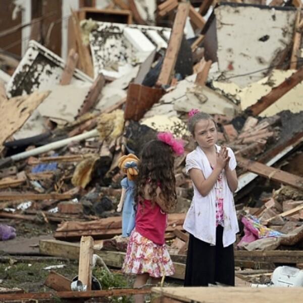 niñas paradas junto a escombros