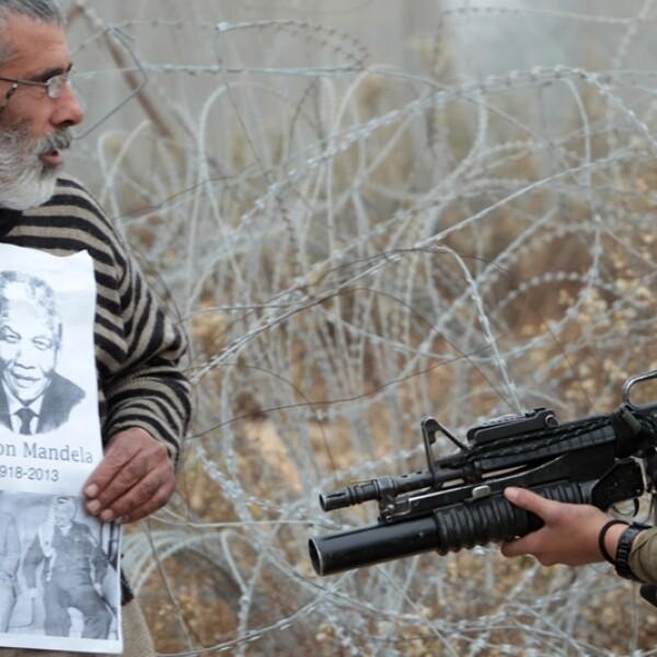 un palestino muestra una fotografia de nelson mandela a soldados israelies