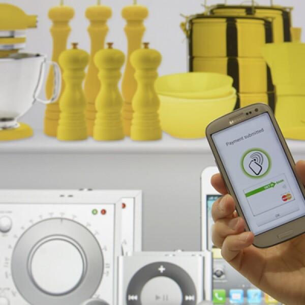 Un empleado posa con un teléfono inteligente para demostrar un sistema de pagos por móviles en el stand de Deutsche Telekom.