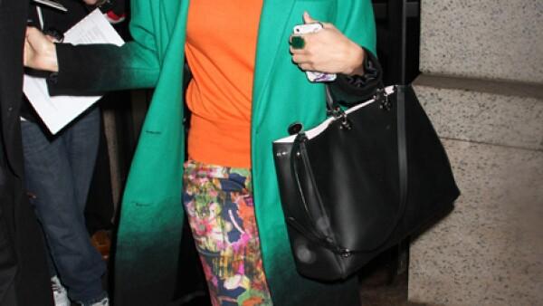 La actriz combina unos pantalones con motivos de flores con un saco verde XL y un suéter naranja.