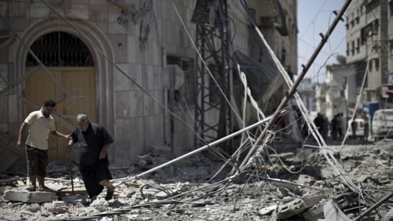 Dos hombres caminan por los escombros de un sector de la Ciudad de Gaza tras un ataque israelita