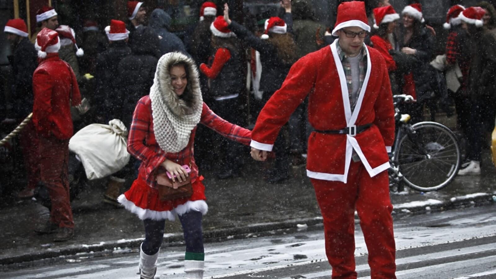 pareja de santas cruza la calle participan en Santacon