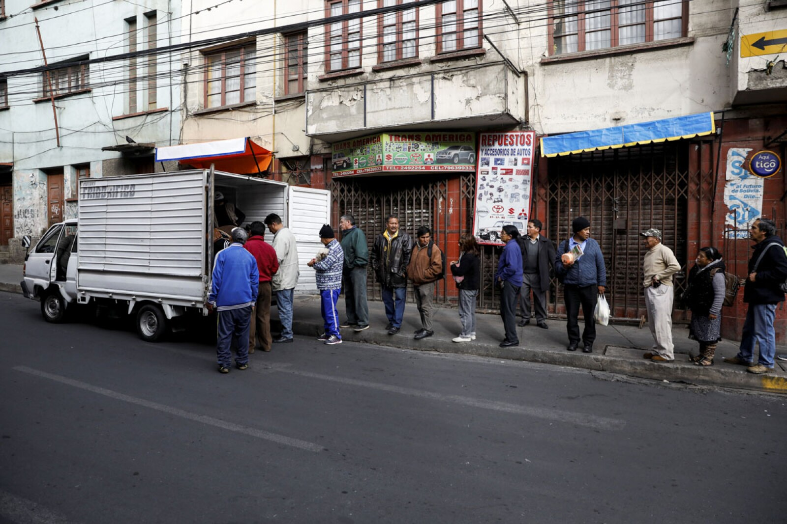 People stand in line to buy bread following Bolivia's former president Evo Morales' exit out of the country, in La Paz