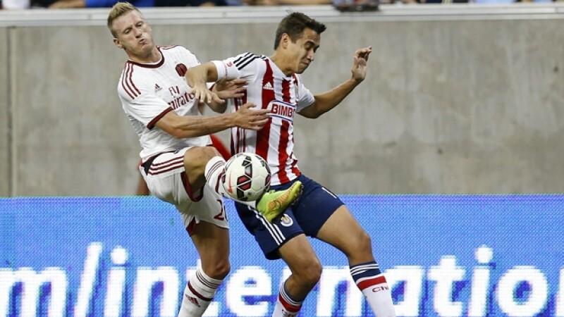 El defensor de Chivas Gerardo Rodríguez disputa un balón con el defensa del AC Milán, Ignazio Abate