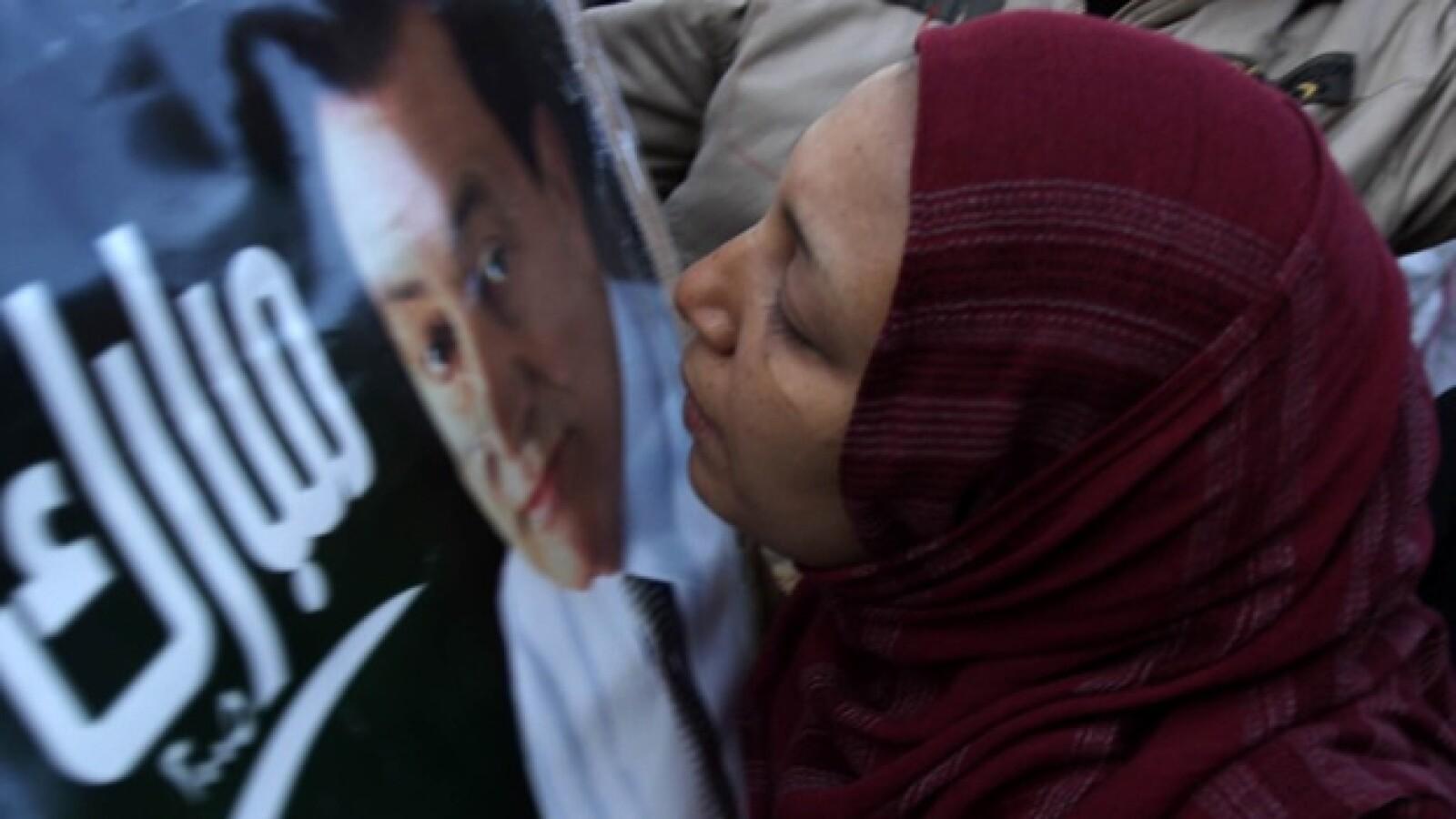 Una mujer besando un cartel de Mubarak