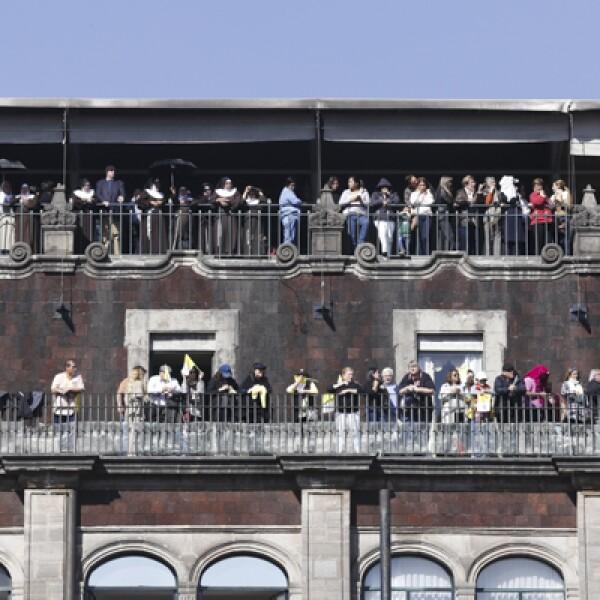Algunas personas se subieron a los edificios alrededor del Zócalo para ver el paso de Francisco este sábado.