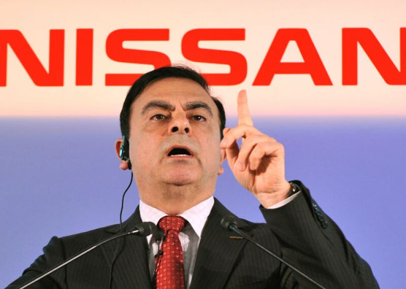 Carlos Ghosn frente a logo de Nissan