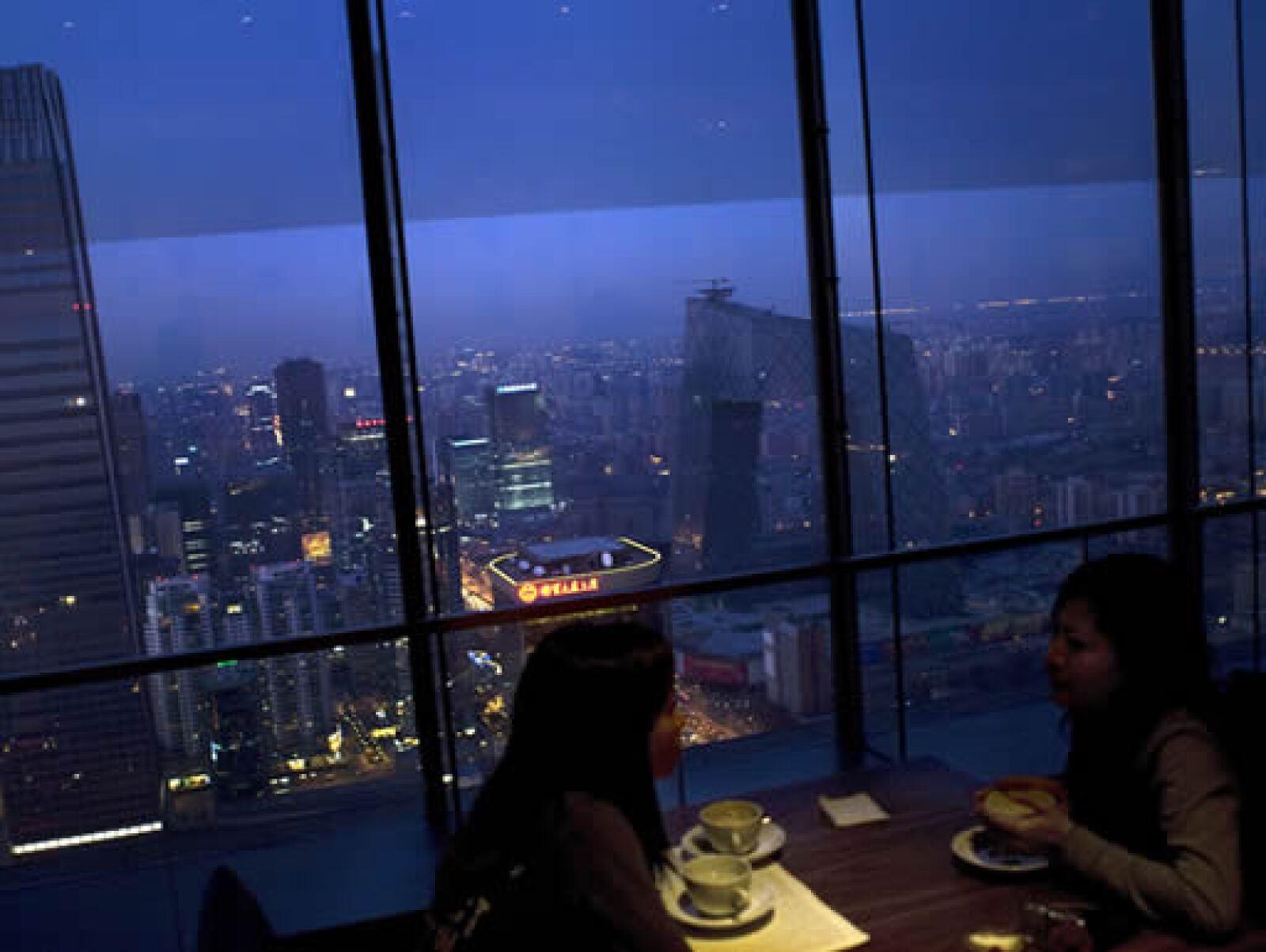 Dos amigas disfrutan de un café en un restaurante con vista a la ciudad de Pekín.