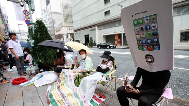 Los consumidores japoneses acamparon afuera de las tiendas y algunos se disfrazaron del porpular teléfono de Apple.