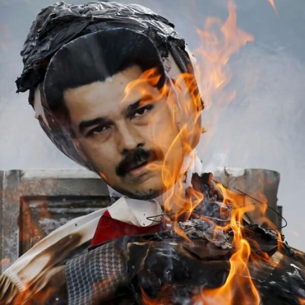 Una efigie con una foto del presidente de Venezuela Nicolás Maduro arde luego de que personas le prendieran fuego