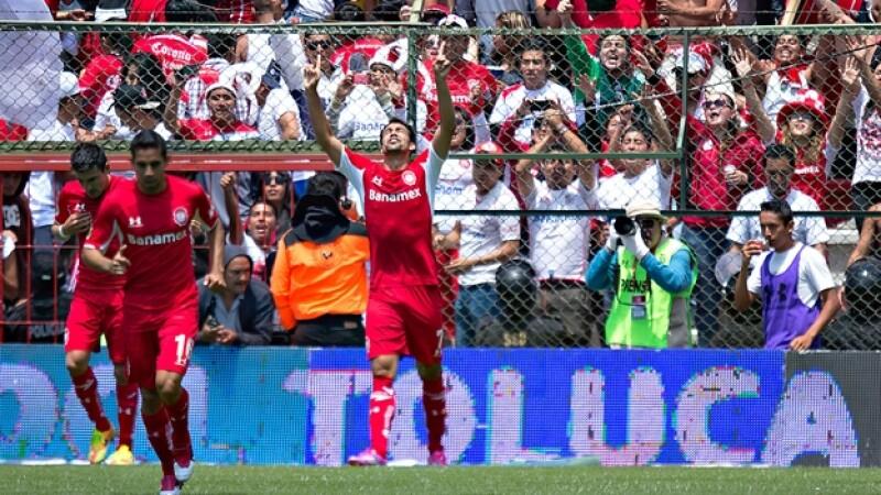 Pablo Velázquez (centro), delantero de Toluca, festeja su segundo gol que le dio el triunfo definitivo a los Diablos Rojos este domingo