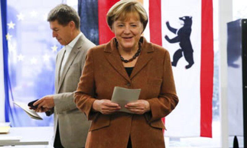 Merkel al depositar su voto este domingo (atrás su esposo) (Foto: Reuters)