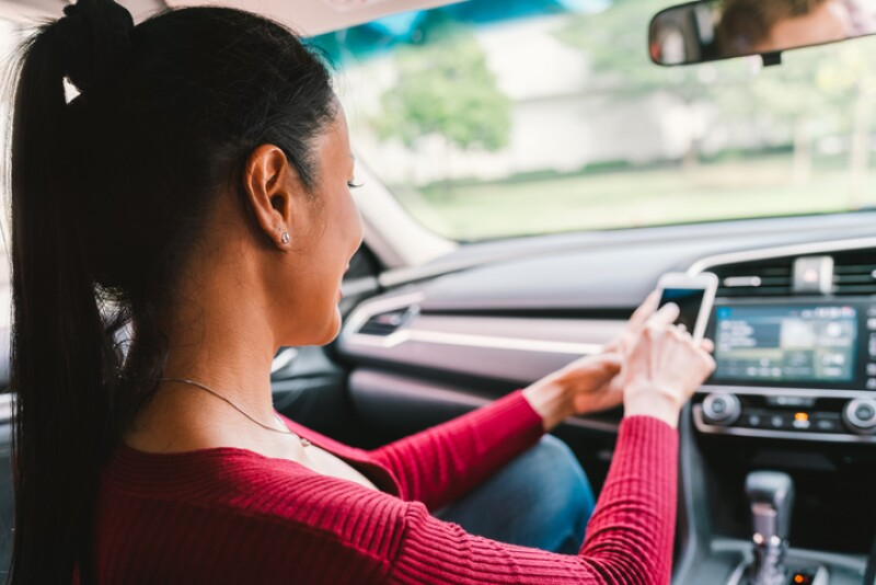 Woman using smartphone app on modern car. Mobile phone application, map navigation device technology, transportation, or crowdsourcing taxi concept