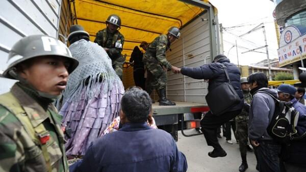 soldados ayuda a la gente a subir a camionestas