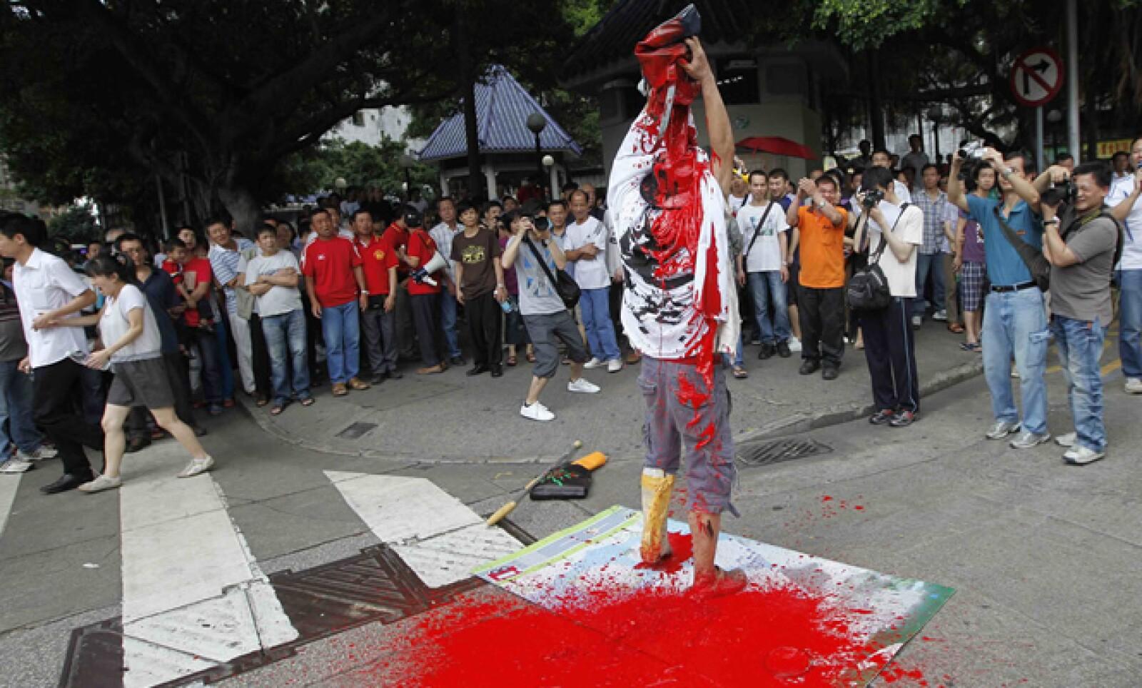 Un manifestante de esta región administrativa especial en China se arrojó pintura durante una protesta contra los trabajadores migrantes de la región continental y otros países, así como la corrupción gubernamental.