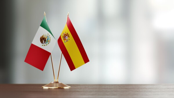 Spanish And Mexican Flag Pair On A Desk Over Defocused Background