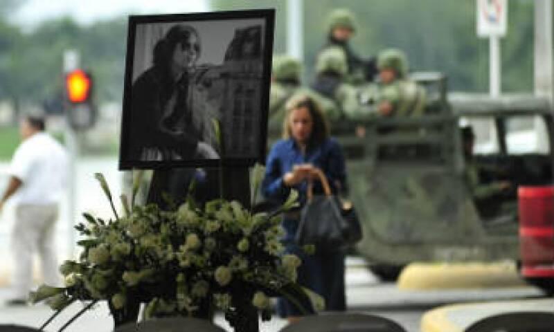 Familiares colocaron flores blancas junto a una fotografía de Michelli Gil.(Foto: AFP)