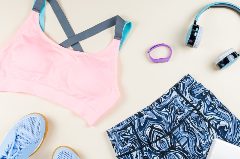 Woman sport bra, leggins, sneakers, headphones and fitness tracker on neutral background. Sport fashion concept.