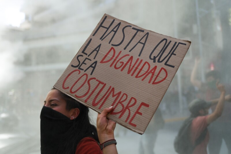 """A demonstrator holds a placard reading """"Until dignity becomes custom"""" during a protest at Providencia, a wealthy neighborhood, in Santiago"""