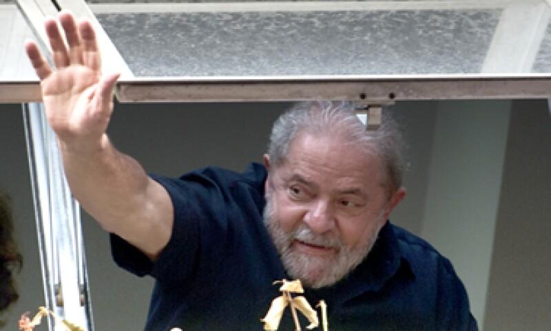 El expresidente de Brasil Lula saluda a sus seguidores que le mostraron apoyo tras el allanamiento en su casa. (Foto: AFP)