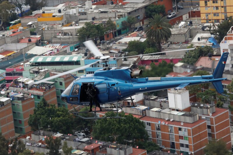"""Police officers, members of a team known as """"Condores"""", stand by the door of the helicopter during a patrol of the city, part of a new strategy to combat the crime in Mexico City,"""