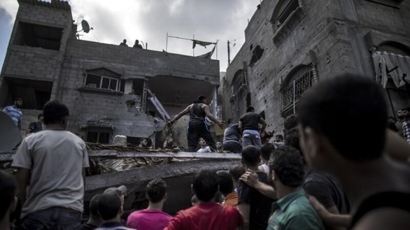 Un grupo de palestinos se reúne alrededor de hogares dañados por misiles lanzados por Israel a Gaza