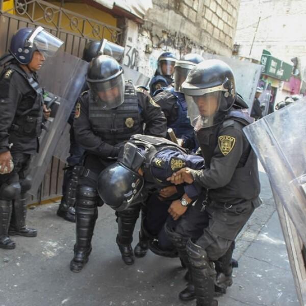 Policías capitalinos cargan a un compañero luego de los enfrentamientos