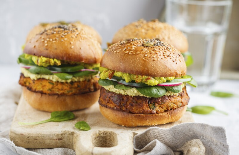 Healthy baked sweet potato burger with whole grain bun, guacamole, vegan mayonnaise and vegetables on a wooden board. Vegetarian food concept, light background.