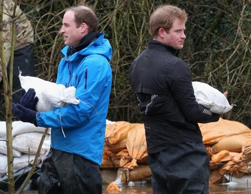 Los príncipes, junto a un grupo de la armada británica, asistieron a una comunidad severamente afectada por las lluvias. En el camino, Guillermo invitó a un reportero a ayudar en lugar de grabarlos.